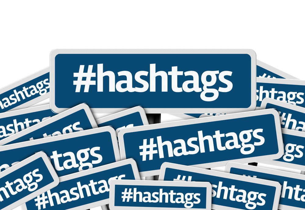 Hashtags written on multiple blue road sign
