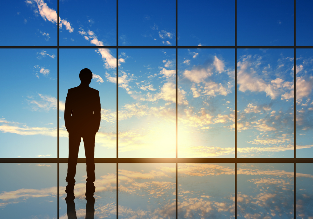 Silhouette of businessman against panoramic office window